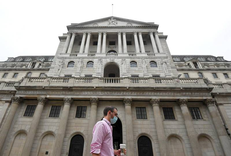 FILE PHOTO: A worker wearing a protective face mask walks past the Bank of England in the City of London, Britain, August 6, 2020. REUTERS/Toby Melville/File Photo