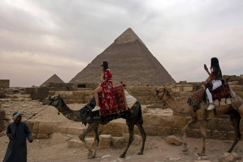 In this Tuesday, March 10, 2020, photo, two foreign women tourists ride camels at the Giza Pyramids near Cairo, Egypt. The country's prime minister announced at a news conference on Tuesday, March 24, 2020, a two-week, 7 p.m. to 6 a.m. curfew for its over 100 million people to slow the spread of the new coronavirus. The 11-hour curfew would go into effect Wednesday across the country and last for two weeks. (AP Photo/Maya Alleruzzo)