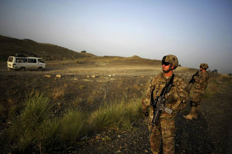 """(FILES) In this file photo members of the 1st Platoon Comanche Company of the US Army stand at a checkpoint in the Combat Outpost Lakon in Buwri Tana District, Khost Province on August 9, 2012.    US President Joe Biden warned that a deadline to withdraw all American soldiers from Afghanistan by May 1, 2021 as part of a deal with the Taliban was possible but """"tough."""" """"Could happen, but it is tough,"""" Biden said when asked in a TV interview broadcast Wednesdayon March 17, 2021. / AFP / Jose CABEZAS"""