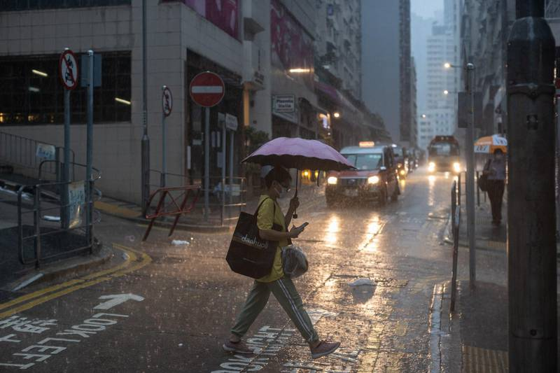 epa09306999 A woman carries an umbrella as she crosses a street during a rain storm in Hong Kong, China, 28 June 2021. The Hong Kong Observatory issued a Black Rainstorm Warning Signal meaning that heavy rain has fallen or is expected to fall, exceeding 70 millimetres in an hour.  EPA/JEROME FAVRE