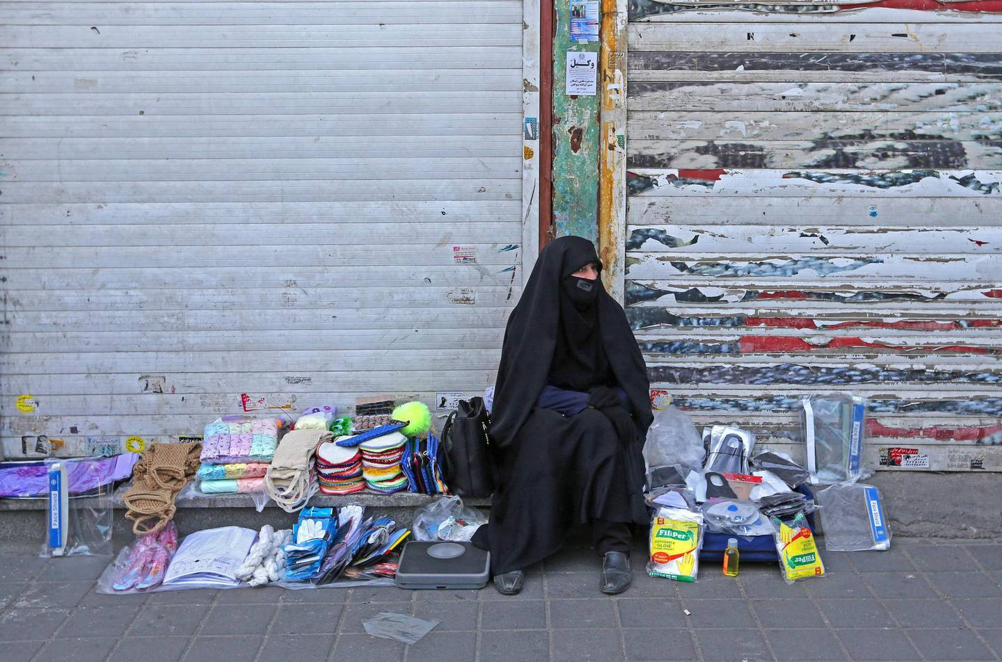 An Iranian street vendor wearing a protective mask amid the novel coronavirus pandemic, sits by her display of goods on a street of the capital Tehran, on May 09, 2020. / AFP / ATTA KENARE