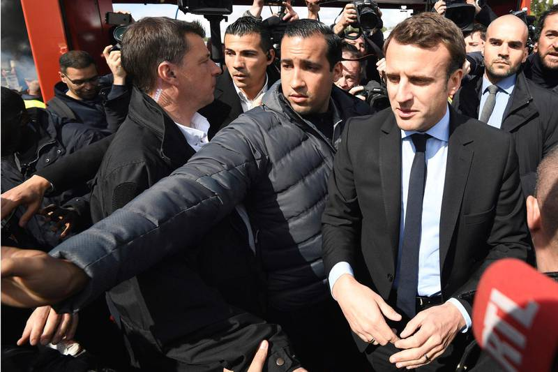 FILE - In this Wednesday April 26, 2017 file photo French centrist presidential election candidate Emmanuel Macron, flanked by his bodyguard, Alexandre Benalla, left, arrives outside the Whirlpool home appliance factory, in Amiens, northern France. Benalla, an aide to President Emmanuel Macron, charged with security, has been seen in a video wearing a police helmet and beating up a student protester in May, reigning criticism on Macron notably due to the light punishment _ a two-week suspension. (Eric Feferberg/Pool via AP, File)