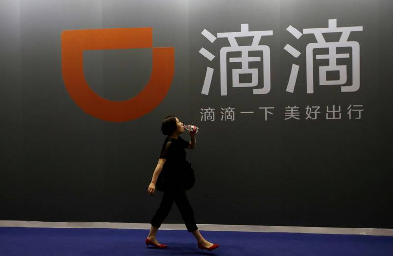 FILE PHOTO: A woman walks past ride-hailing company Didi Chuxing's booth at the Global Mobile Internet Conference (GMIC) 2017 in Beijing, China April 28, 2017. REUTERS/Jason Lee/File Photo