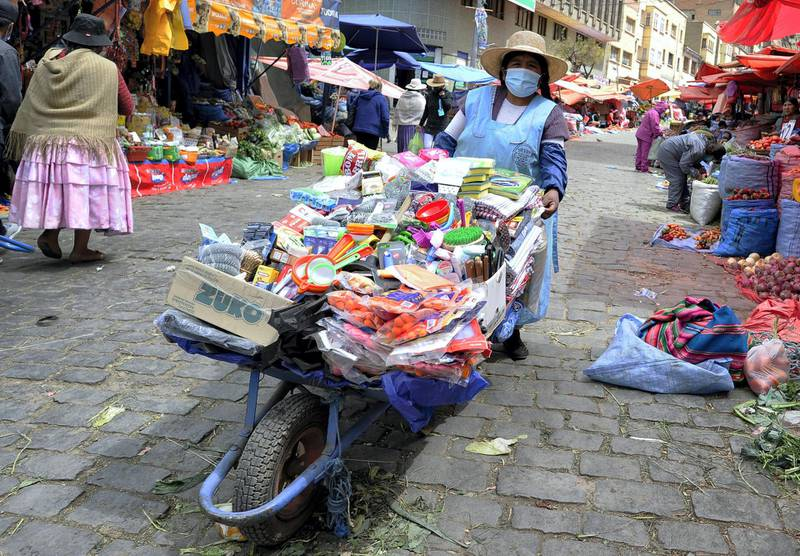 An Aymara indigenous woman wears a face mask as she offers cleaning products for sale at the Rodriguez Market in La Paz on September 1, 2020, amid the new coronavirus pandemic. - Bolivia's interim government eased lockdown measures since September 1, extending circulation and store times and opening air borders. (Photo by JORGE BERNAL / AFP)