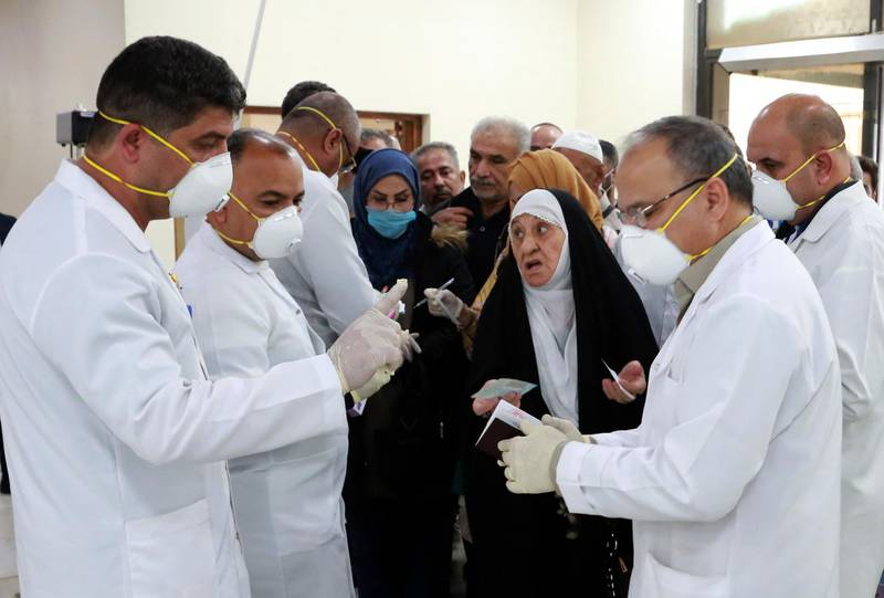 epa08244101 Members of Iraqi medical team check passengers upon arrival from Iran at Baghdad international airport in Baghdad, Iraq, 24 February 2020. According to reports, Iraqi health authorities said on 24 February that an Iranian national in the city of Najaf tested positive for the coronavirus, becoming the first confirmed case of the COVID-19 disease in the country. Iraqi authorities have taken action to screen those arriving at the airports and border crossings with Iran, while the Iraqi airlines canceled all flights to Iran, following the cases of the deadly Covid-19 Coronavirus diagnosed in Iran.  EPA/AHMED JALIL