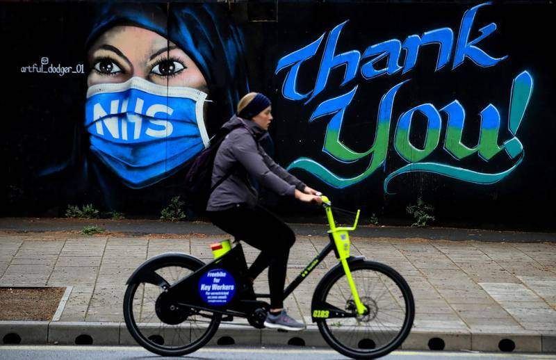 LONDON, ENGLAND  - APRIL 29: A woman cycles past a piece of street art, created by The Artful Dodger, thanking the NHS on April 29, 2020 in London, England. British Prime Minister Boris Johnson, who returned to Downing Street this week after recovering from Covid-19, said the country needed to continue its lockdown measures to avoid a second spike in infections. (Photo by Andrew Redington/Getty Images)