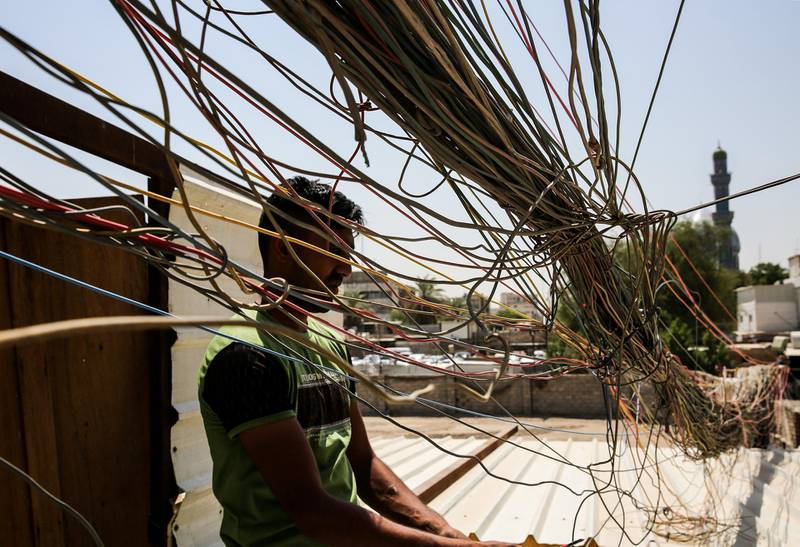 (FILES) In this file photo taken on July 29, 2018, a man checks the wiring on electric cables reaching out to homes in Saadoun Street in the Iraqi capital Baghdad, as chronic power shortages have forced residents to buy electricity from private entrepreneurs who run generators on street corners across the country. With a freshman at the helm, Iraq's electricity ministry is planning a long-awaited overhaul of the broken sector to both meet US pressure to halt Iranian power imports and head off summertime protests over chronic cuts. Baghdad hopes it will generate enough megawatts to feed demand by summer, when cuts can leave millions powerless for up to 20 hours per day. / AFP / SABAH ARAR