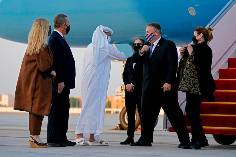 UAE's Protocol Chief Shihab al-Faheem greets with an elbow-bump US Secretary of State Mike Pompeo (C-R) alongside his wife Susan (R) in the presence of US Ambassador to the United Arab Emirates John Rakolta (L) and his wife Terry, at al-Bateen Executive Airport in Abu Dhabi on November 20, 2020.  / AFP / POOL / Patrick Semansky