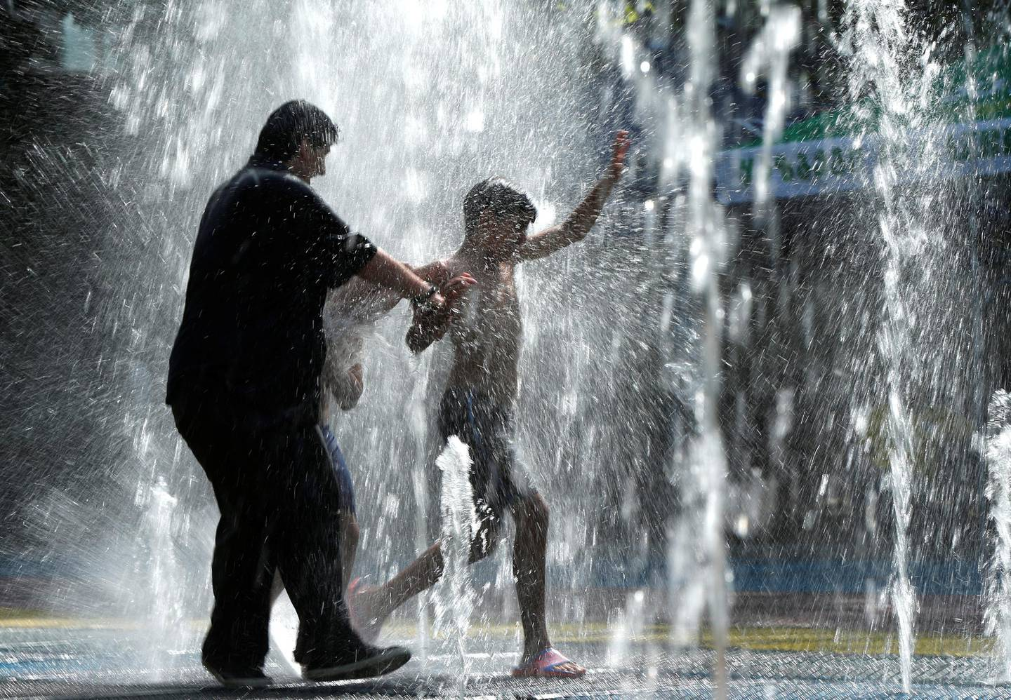 People cool off in a water fountain on a hot summer day in Tbilisi, Georgia, July 2, 2018. REUTERS/David Mdzinarishvili