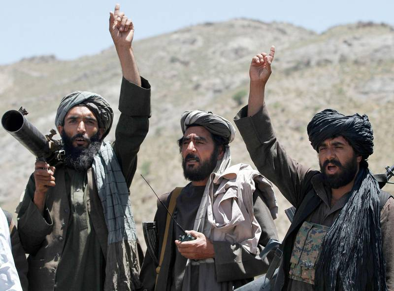 FILE - In this May 27, 2016 file photo, Taliban fighters react to a speech by their senior leader in the Shindand district of Herat province, Afghanistan. With U.S. support, the Afghan government has made a surprising new peace offer to the Taliban, only to immediately run into a wall. The insurgents show no sign of shifting from their demand that talks for a conflict-ending compromise take place with Washington, not Kabul.  (AP Photos/Allauddin Khan, File)