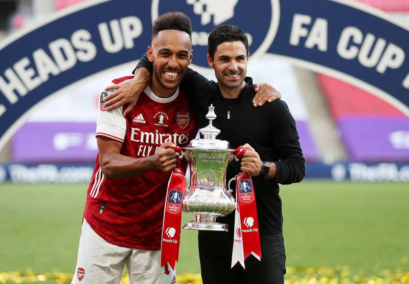 FILE PHOTO: Soccer Football - FA Cup Final - Arsenal v Chelsea - Wembley Stadium, London, Britain - August 1, 2020 Arsenal manager Mikel Arteta and Pierre-Emerick Aubameyang celebrate with the trophy after winning the FA Cup, as play resumes behind closed doors following the outbreak of the coronavirus disease (COVID-19) Pool via REUTERS/Catherine Ivill/File Photo