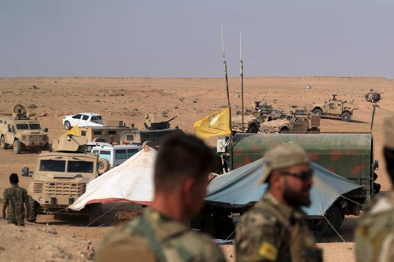 """Coalition forces and members of the Syrian Democratic Forces (SDF) gather at their operation room near the village of Susah in the eastern province of Deir Ezzor, near the Syrian border with Iraq on September 13, 2018. - US-backed fighters are fighting in Deir Ezzor to oust Islamic State jihadists from the town of Hajin on the east bank of the Euphrates, the most significant remnant of the sprawling """"caliphate"""" the jihadists once controlled spanning Syria and Iraq. (Photo by AFP)"""