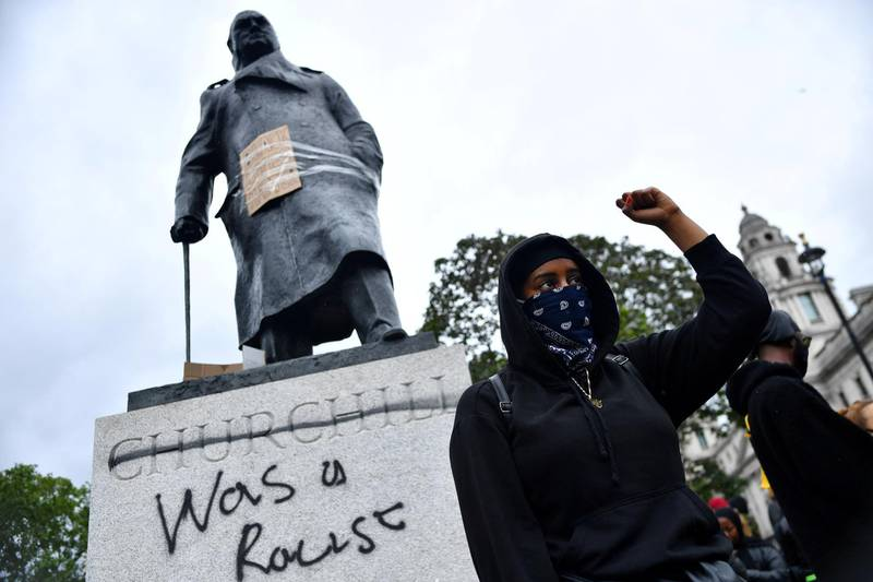 FILE PHOTO: A demonstrator reacts infront of graffiti on a statue of Winston Churchill in Parliament Square during a Black Lives Matter protest in London, following the death of George Floyd who died in police custody in Minneapolis, London, Britain, June 7, 2020. REUTERS/Dylan Martinez     TPX IMAGES OF THE DAY - RC2G4H9061BN/File Photo