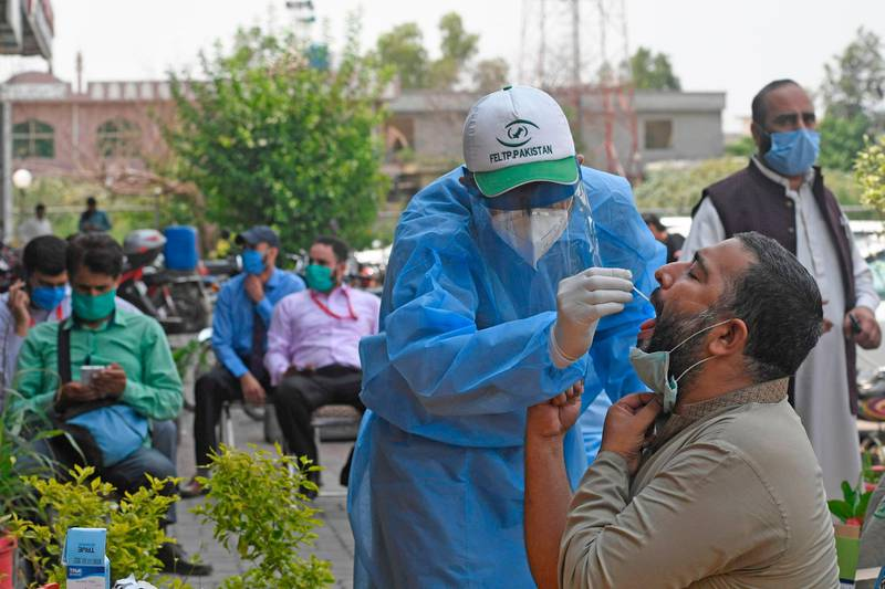 """A health official wearing protective gear takes the sample of a man at a drive-through screening and testing facility for the COVID-19 coronavirus, alongside a street in Islamabad on June 10, 2020. The World Health Organization has told Pakistan it should implement """"intermittent"""" lockdowns to counter a surge in coronavirus infections that has come as the country loosens restrictions, officials said. / AFP / Aamir QURESHI"""