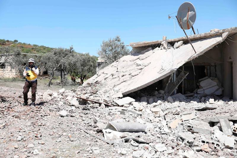 A member of the Syrian Civil Defence, also known as the White Helmets, walks amidst the debris of homes following bombardment by regime forces on the village of Basamis in the Idlib province on May 4, 2019. The civil war in Syria has killed more than 370,000 people and displaced millions since it began in 2011 with anti-regime protests that sparked a devastating crackdown. / AFP / OMAR HAJ KADOUR