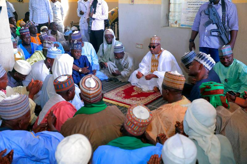 Babagana Umara Zulum, center, governor of Borno State, prays during a funeral for those killed by suspected Boko Haram militants in Zaabarmar, Nigeria, Sunday, Nov. 29, 2020. Nigerian officials say suspected members of the Islamic militant group Boko Haram have killed at least 40 rice farmers and fishermen while they were harvesting crops in northern Borno State. The attack was staged Saturday in a rice field in Garin Kwashebe, a Borno community known for rice farming. (AP Photo/Jossy Ola)