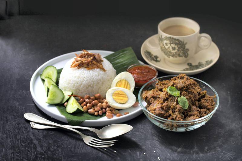 Nasi lemak (Malay fragrant rice dish cooked in coconut milk and pandan leaf) on rustic wooden table top along side with recipe ingredient. Flat lay image with negative space.