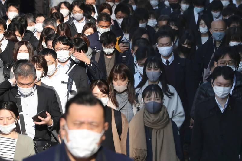 Commuters wearing face masks to protect against the spread of the coronavirus walk on a street in Tokyo, Tuesday, Nov. 17, 2020. Japan has set a record for its daily new cases exceeding 2,100 cases of the coronavirus, the health ministry said Thursday, Nov. 19, 2020 as Japanese Prime Minister Yoshihide Suga called for maximum caution but without asking for restrictions on traveling or business activities. (AP Photo/Koji Sasahara)