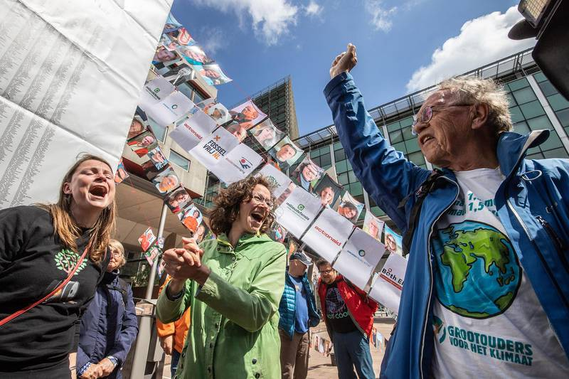 Members of the environmental group MilieuDefensie celebrate the verdict of the Dutch environmental organisation's case against Royal Dutch Shell Plc, outside the Palace of Justice courthouse in The Hague, Netherlands, on Wednesday, May 26, 2021. Shellwas ordered by a Dutch court to slash its emissions harder and faster than planned, dealing a blow to the oil giant that could have far reaching consequences for the rest of the global fossil fuel industry. Photographer: Peter Boer/Bloomberg