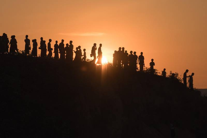 """TOPSHOT - Rohingya Muslim refugees  walk down a hillside in the  Kutupalong refugee camp in Cox's Bazar on November 26, 2017. Rohingya refugees who return to Myanmar from Bangladesh following a repatriation agreement will initially live in temporary shelters or camps, Dhaka said November 25, a day after the UN raised concern for their safety when they go back. The United Nations says more than 620,000 Rohingya have fled to Bangladesh since August and now live in squalor in the world's largest refugee camp after a military crackdown in Myanmar that the UN and Washington have said clearly constitutes """"ethnic cleansing"""". / AFP PHOTO / Ed JONES"""