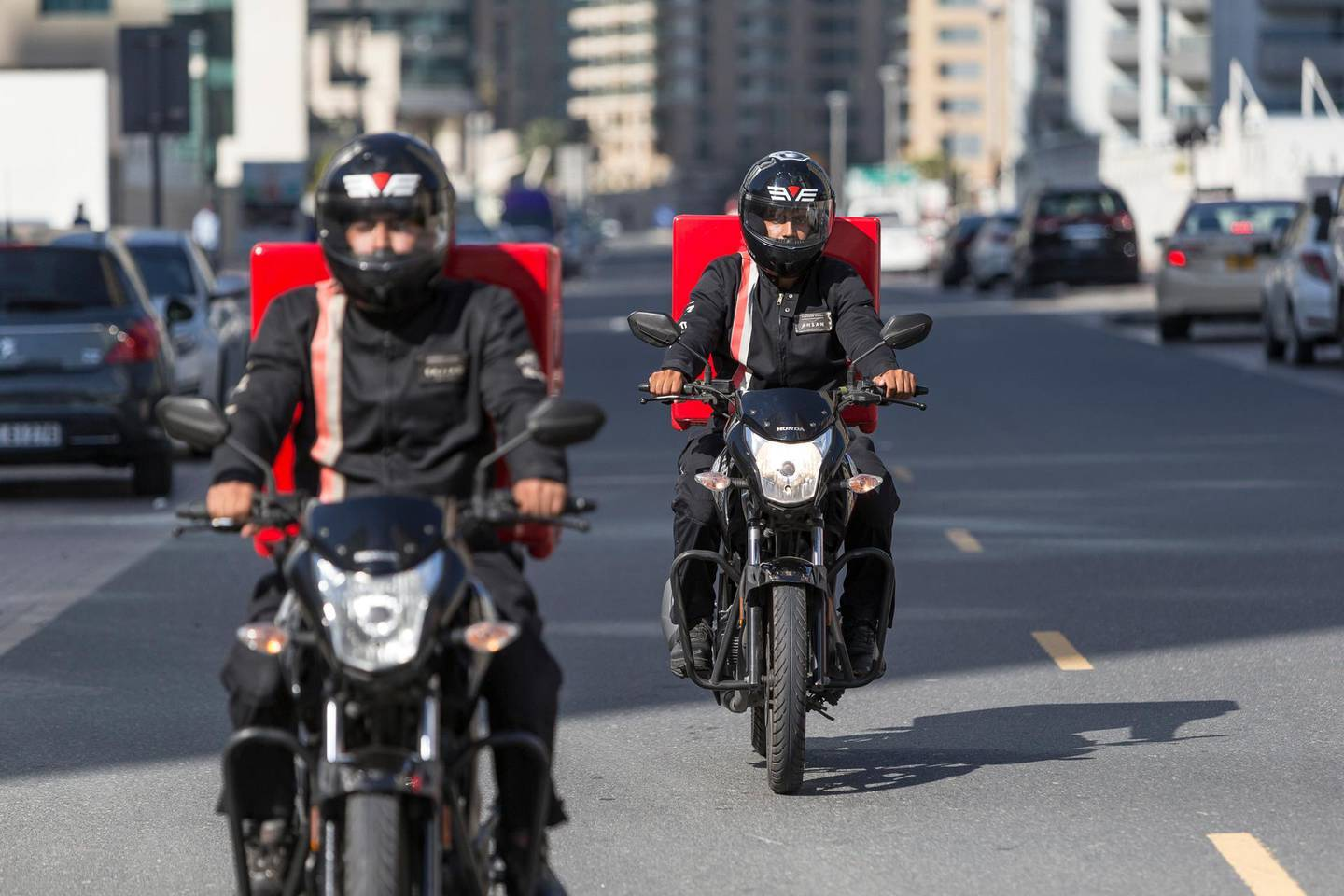 """DUBAI, UNITED ARAB EMIRATES, 21 APRIL 2016. A bike safety campaign called Safety Delivered where delivery drivers were asked who were important in their lives, and were given helmets with pictures of their family and words such """"I am a son"""" and """"I am a father"""". The aim is to remind the drivers that they have people counting on them to be safe while they are out on the road. Sajjad Hussein (front) and Ahsan Akhbar (Back) both from Pakistan ride  with their helmets and delivery bikes. (Photo: Antonie Robertson/The National) ID: 44814. Journalist: Ramona Ruiz. Section: National. *** Local Caption ***  AR_2104_Delivery_Bike_Safety-17.JPG"""