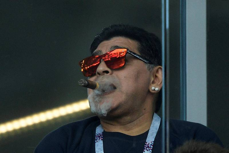 (FILES) In this file picture taken on June 16, 2018 Argentina's football legend Diego Maradona smokes a cigare as he attends the Russia 2018 World Cup Group D football match between Argentina and Iceland at the Spartak Stadium in Moscow. Argentine football legend Diego Maradona turns 60 on October 30, 2020.   - RESTRICTED TO EDITORIAL USE - NO MOBILE PUSH ALERTS/DOWNLOADS  / AFP / Juan Mabromata / RESTRICTED TO EDITORIAL USE - NO MOBILE PUSH ALERTS/DOWNLOADS