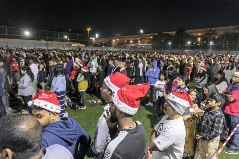 DUBAI, UNITED ARAB EMIRATES. 25 DECEMBER 2019. Midnight Mass at St Mary's in Dubai to celebrate Christmas. The overflow crowd takes to the churches football field to watch the Mass on big screens. (Photo: Antonie Robertson/The National) Journalist: None. Section: National.