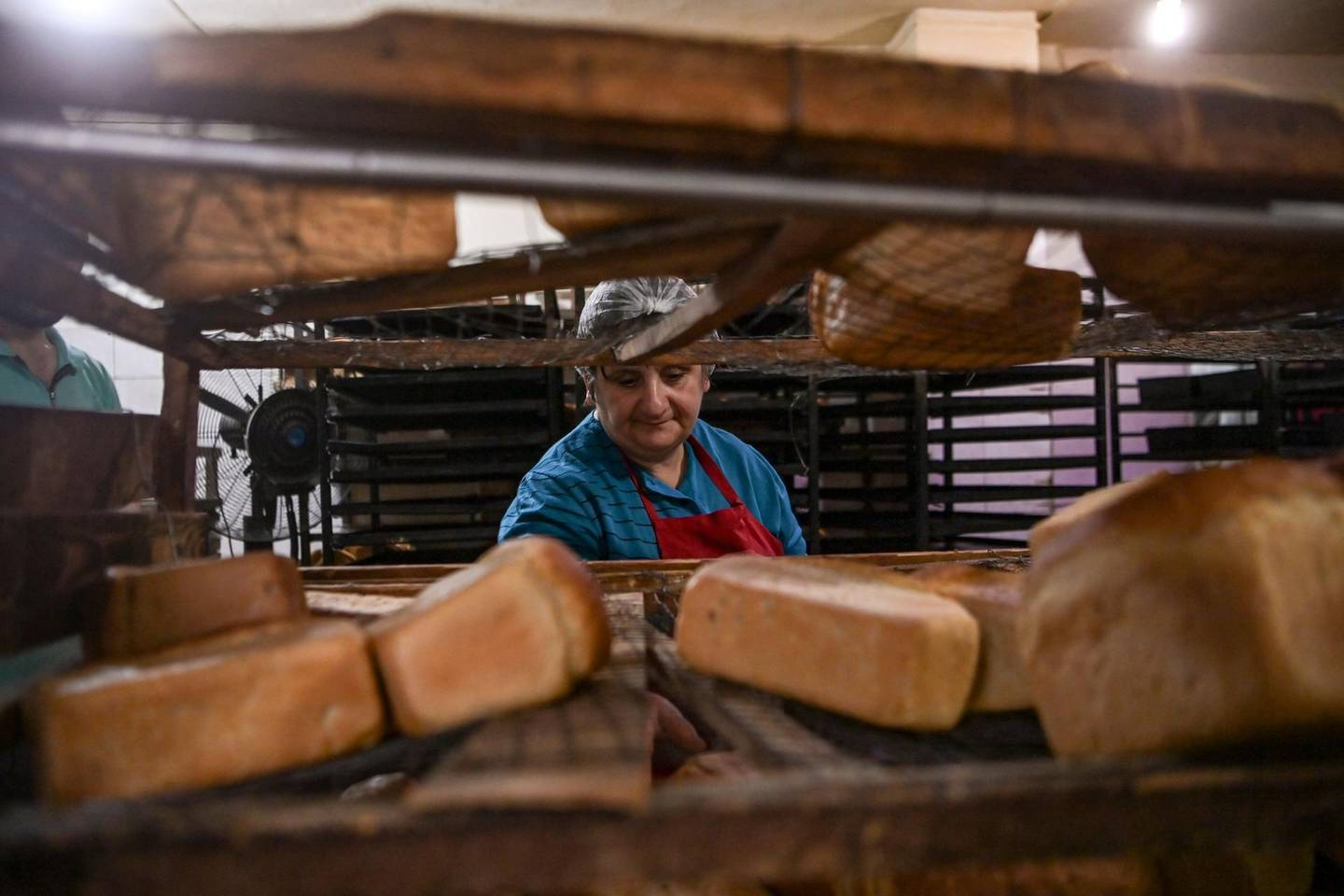 A woman makes bread at a bakery in the city of Stepanakert, that works 24 hours a day to offer free bread to the remain residents and delivering - when needed - to the cities of Martuni and Martakert, on October 21, 2020, during the ongoing fighting between Armenia and Azerbaijan over the breakaway region of Nagorno-Karabakh. / AFP / ARIS MESSINIS