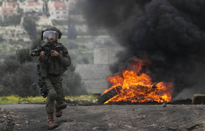 An Israeli soldier runs toward Palestinian demonstrators during clashes with them, following a demonstration against the expropriation of Palestinian land by Israel, in the village of Kfar Qaddu near the city of Nablus in the Israeli occupied West Bank,  on March 6, 2020. / AFP / JAAFAR ASHTIYEH