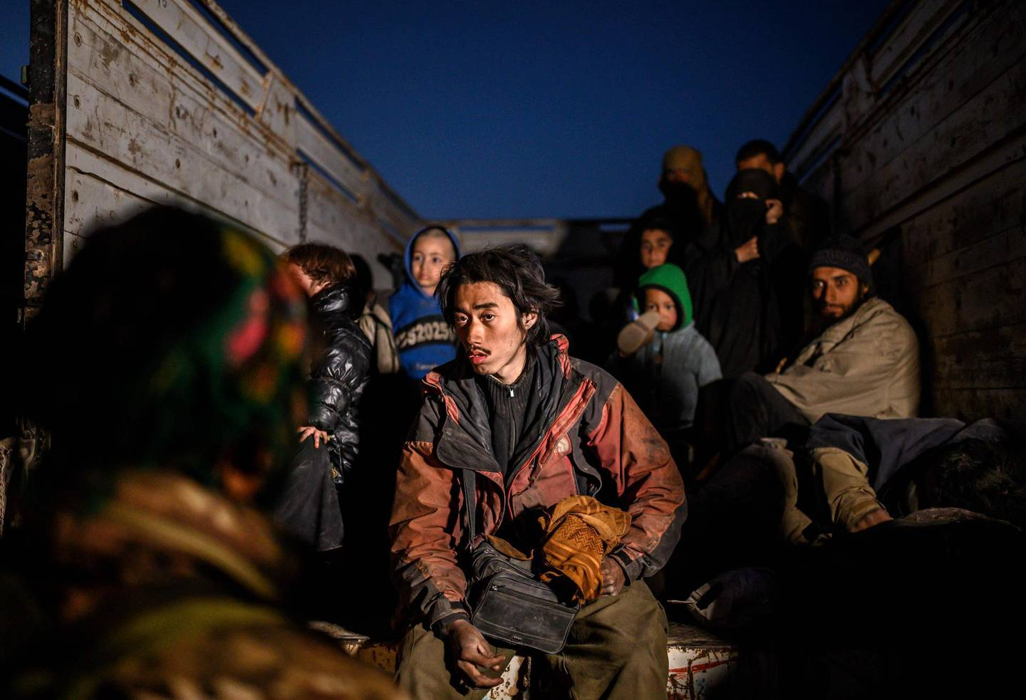 """TOPSHOT - A man (C) suspected of belonging to the Islamic State (IS) group, who spoke to AFP journalists in French, sits in the back of a truck as he waits to be searched by members of the Kurdish-led Syrian Democratic Forces (SDF) just after leaving IS' last holdout of Baghouz, in the eastern Syrian province of Deir Ezzor on March 4, 2019. The capture of Baghouz would mark the end of IS territorial control in the region and deal a death blow to the """"caliphate"""", which once covered huge swathes of Syria and Iraq. / AFP / Bulent KILIC"""