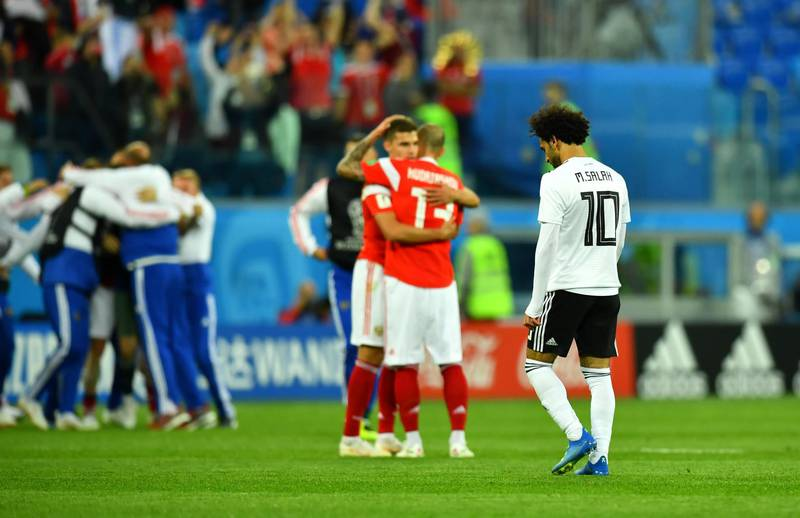 Soccer Football - World Cup - Group A - Russia vs Egypt - Saint Petersburg Stadium, Saint Petersburg, Russia - June 19, 2018   Egypt's Mohamed Salah looks dejected after the match as Russia players celebrate   REUTERS/Dylan Martinez