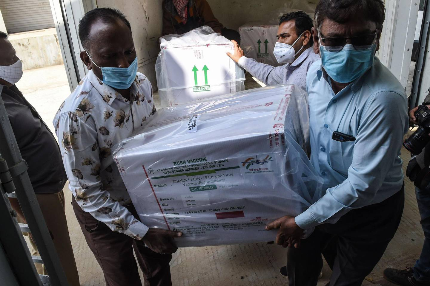 Officials unload boxes containing Covishield vaccine at the Regional Vaccine Store in Ahmedabad on January 12, 2021. / AFP / SAM PANTHAKY