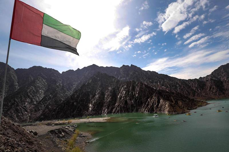 """This picture taken on February 15, 2019 shows an Emirati national flag flying over the  reservoir at the Hatta Dam where kayaks and boats are cruising, in the Dubai emirate's exclave of Hatta, near the Omani border. Some 100 kilometres from Dubai's skyscrapers, """"glamping"""" in luxurious trailer-style set-ups and mountainside lodgings is the next big thing in the desert country. Betting on tourism at a time of low oil prices, Dubai has pushed a blend of camping and luxury hotels -- """"glamping"""", short for """"glamourous camping"""". The city welcomed a record 15.92 million visitors in 2018, many of whom were drawn to its mega malls, luxurious hotels and pristine beaches. / AFP / KARIM SAHIB"""