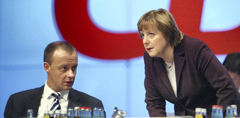 LEIPZIG, GERMANY - DECEMBER 2:  Friedrich Merz (L), head of the Christian Democratic Union (CDU) faction in the Bundestag and Angela Merkel, head of the party, speak prior to Merz's speech on tax reform at the CDU party congress December 2, 2003 in Leipzig, Germany. The CDU, Germany's main opposition party, is proposing a string of counter reforms in response to the social and economic reform plans of the current Social Democrat/Green government. (Photo Sean Gallup/Getty Images)