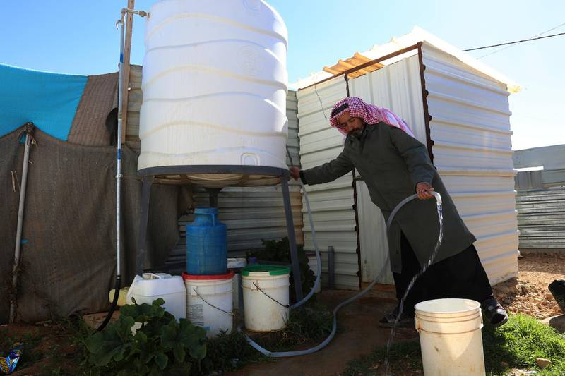 A Syrian man fills a bucket with water inside Zaatari, the largest camp for Syrian refugees in Mafraq, Jordan, Sunday, Feb. 3, 2019.  UNICEF says a project funded by Germany, Canada, UK and US, and led by Jordanian authorities, has connected all households in the sprawling camp to both water and sewage networks, making it the first such camp.(AP Photo/Raad Adayleh)