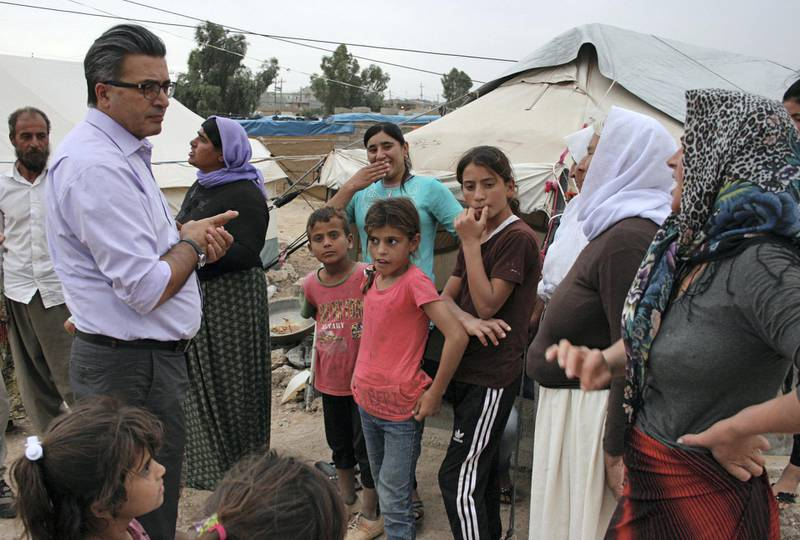 German Traumatologist Jan Ilhan Kizilhan speaking to Yazidi refugees on the outskirts of the northern town of Khanike, Iraq, 7 October 2015. The people fled their villages after they were attacked by terrorist militia IS in August 2014 and are now living in an unofficial camp.  PHOTO: STEFANIE JAERKEL/DPA   usage worldwide   (Photo by Stefanie Järkel/picture alliance via Getty Images)