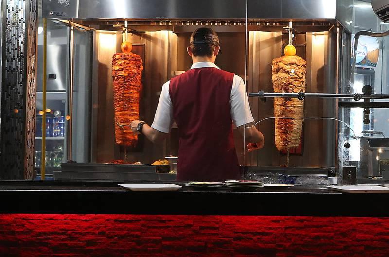 DUBAI , UNITED ARAB EMIRATES – May 18 , 2017 : Worker preparing chicken shawarma at the Al Abra cafeteria in Deira Dubai during the evening in Dubai. ( Pawan Singh / The National ) For News / Photo Feature. ID No :- 19078 *** Local Caption ***  PS1805- DUBAI CREEK44.jpg