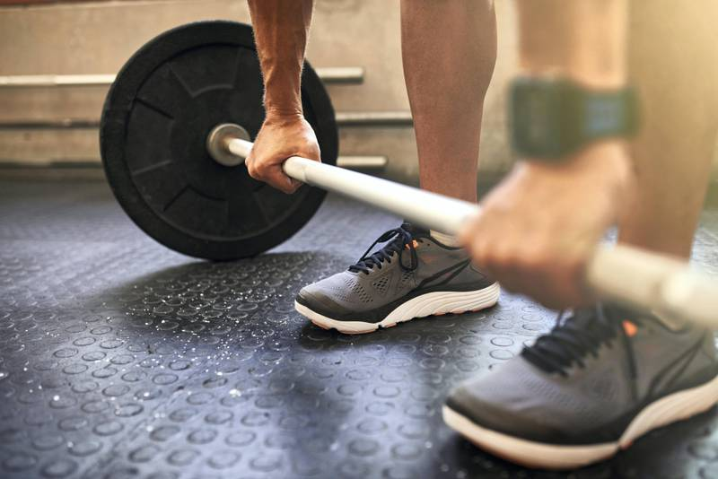 Cropped shot of an unrecognizable man lifting weights at the gym