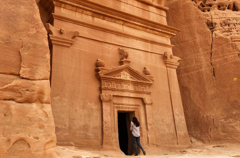 A picture taken on March 31, 2018 shows a journalist taking a photo of a tomb at Madain Saleh, a UNESCO World Heritage site, near Saudi Arabia's northwestern town of al-Ula. - Al-Ula, an area rich in archaeological remnants, is seen as a jewel in the crown of future Saudi attractions as the austere kingdom prepares to issue tourist visas for the first time -- opening up one of the last frontiers of global tourism. Saudi Crown Prince Mohammed bin Salman is set to sign a landmark agreement with Paris on April 10, 2018 for the touristic and cultural development of the northwestern site, once a crossroads of ancient civilisations. (Photo by FAYEZ NURELDINE / AFP)