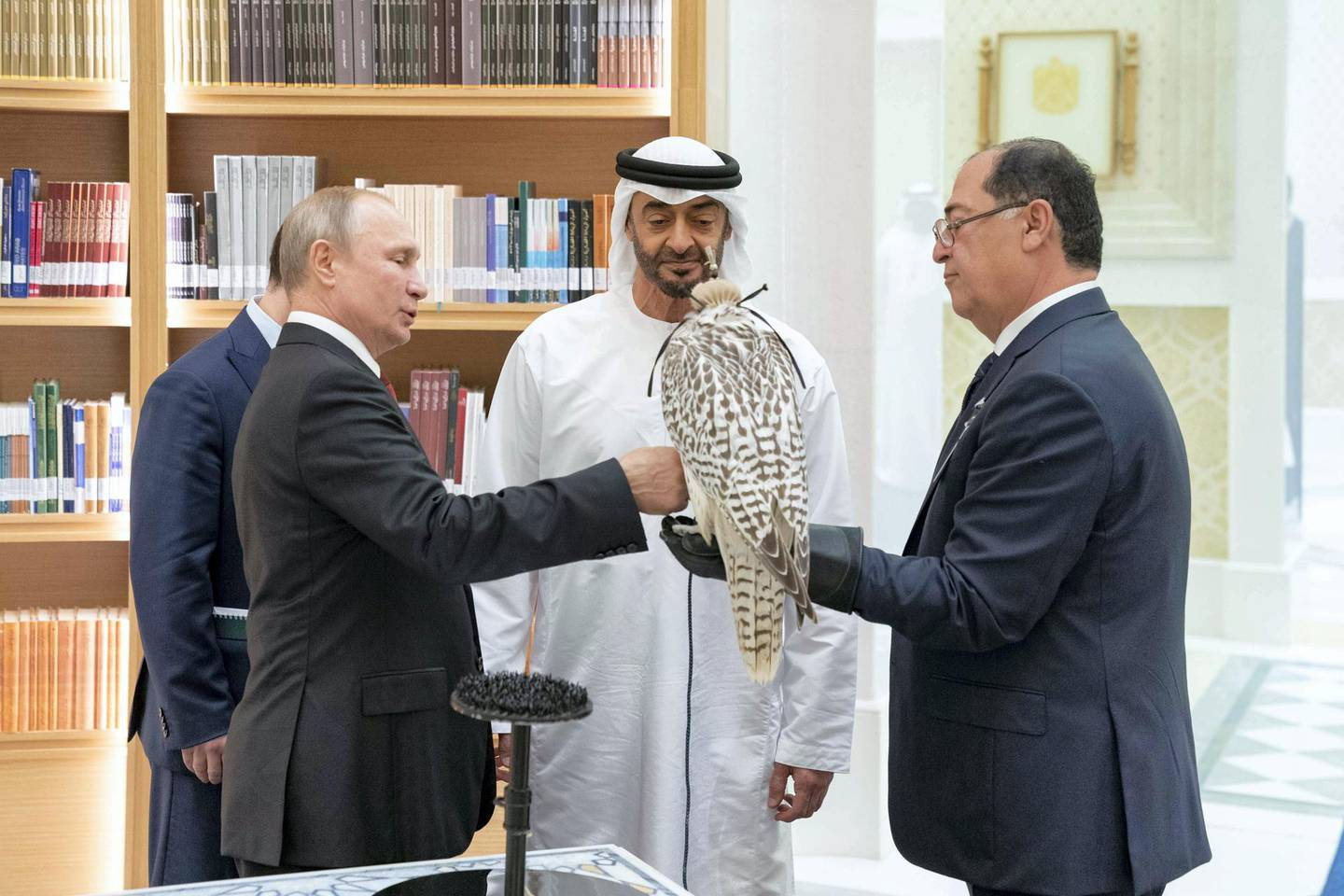 ABU DHABI, UNITED ARAB EMIRATES - October 15, 2019: HH Sheikh Mohamed bin Zayed Al Nahyan, Crown Prince of Abu Dhabi and Deputy Supreme Commander of the UAE Armed Forces (C) and HE Vladimir Putin Vladimirovich, President of Russia (L), exchange gifts during a state visit at Qasr Al Watan.( Mohamed Al Hammadi / Ministry of Presidential Affairs )---