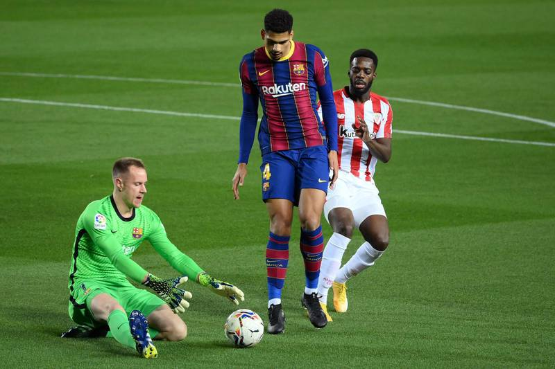 Athletic Bilbao's Spanish forward Inaki Williams (R) challenges Barcelona's Uruguayan defender Ronald Araujo in front of Barcelona's German goalkeeper Marc-Andre ter Stegen during the Spanish league football match FC Barcelona against Athletic Club Bilbao at the Camp Nou stadium in Barcelona on January 31, 2021. (Photo by LLUIS GENE / AFP)