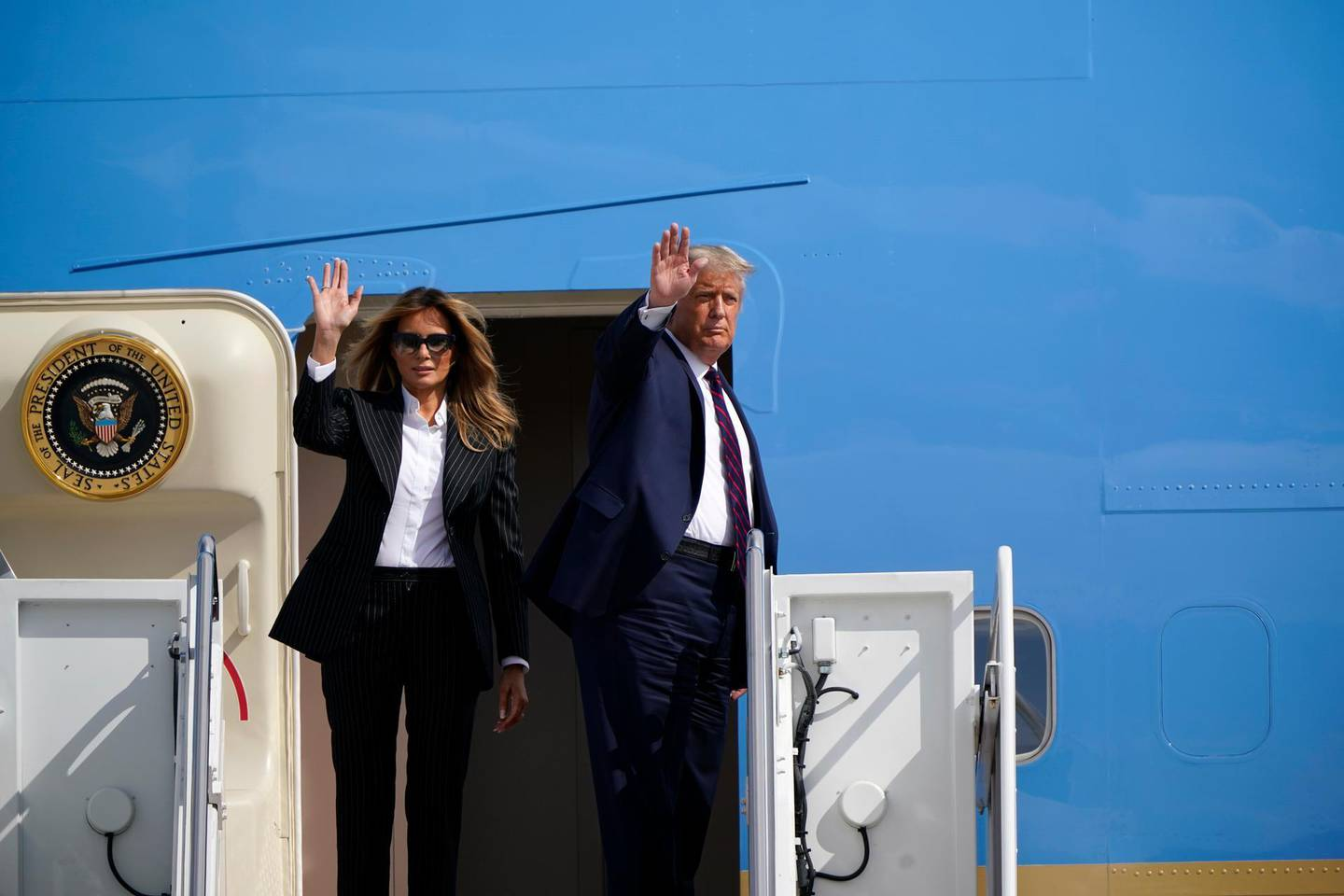 President Donald Trump and first lady Melania Trump wave before boarding Air Force One to travel to the first presidential debate in Cleveland, Tuesday, Sept. 29, 2020, in Andrews Air Force Base, Md. (AP Photo/J. Scott Applewhite)