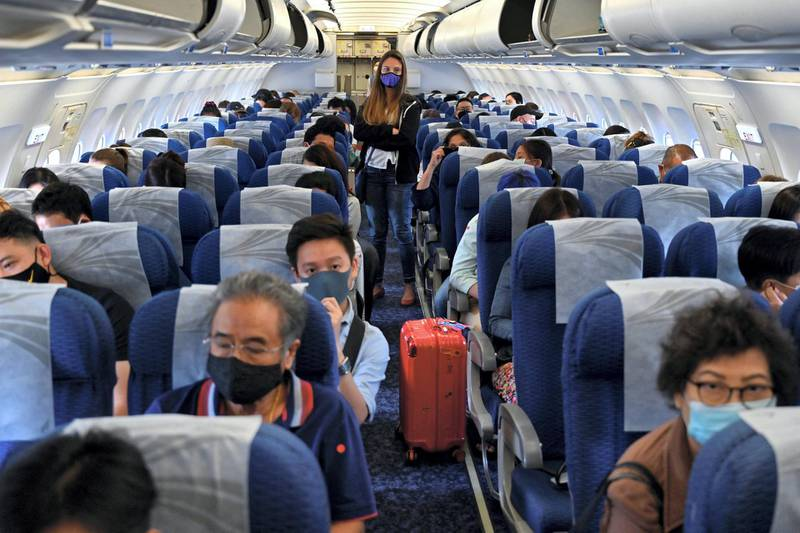 This photo taken on August 16, 2020 shows passengers wearing face masks as a preventive measure against the COVID-19 coronavirus waiting to disembark from a Bangkok Airways domestic flight on arrival at Koh Samui airport in Koh Samui, southern Thailand. (Photo by Romeo GACAD / AFP)