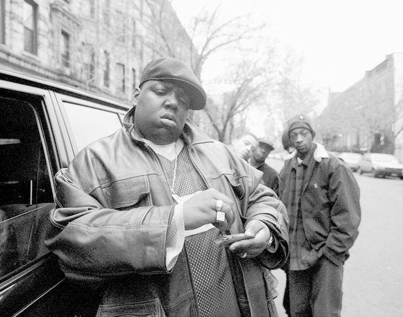 American rapper Notorious B.I.G., aka Biggie Smalls, aka Chris Wallace (1972 - 1997), rolls a cigar outside his mother's house in Brooklyn, New York, 18th January 1995.  (Photo by Clarence Davis/NY Daily News Archive via Getty Images)