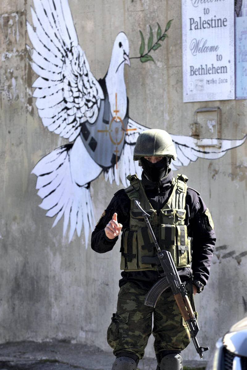 epa07265367 An armed Palestinian policeman stands before a graffiti painting thought to have been painted by the artist known as Banksy that shows a Peace dove wearing a flak jacket with a crosshairs on the bird's chest, painted on a wall at the entrance to the West Bank city of Bethlehem, 06 January 2019. Orthodox believers celebrate Christmas Day on 07 January, according to the Julian calendar.  EPA-EFE/JIM HOLLANDER *** Local Caption *** 54877577