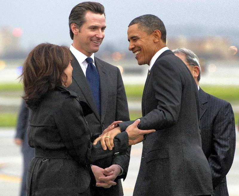 US President Barack Obama greets California Attorney General Kamala Harris (L) and Gavin Newsom, Lieutenant Governor of California, after arriving on Air Force One at San Francisco International Airport in San Francisco, California, February 17, 2011. Obama is traveling on a two-day trip to the West Coast, where he will meet with technology business leaders in California and tour an Intel plant in Oregon. AFP PHOTO / Saul LOEB (Photo by SAUL LOEB / AFP)