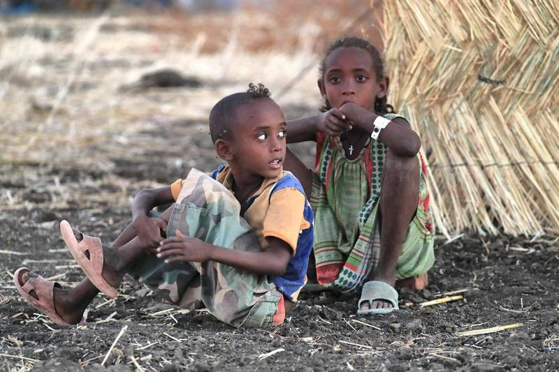 A picture taken on Coptic Christmas eve shows Ethiopian children sitting outside their family's tent at Um Raquba refugee camp in Gedaref, eastern Sudan, on January 6, 2021. (Photo by ASHRAF SHAZLY / AFP)