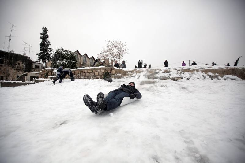 A Palestinian man slides on snow in the old city of Jerusalem on January 10, 2013. Jerusalem was transformed into a winter wonderland after heavy overnight snowfall turned the Holy City and much of the region white, bringing hordes of excited children onto the streets. AFP PHOTO/AHMAD GHARABLI