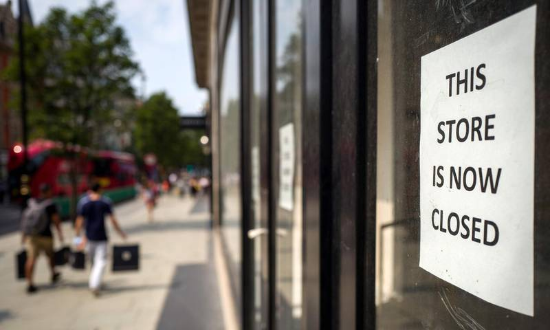 """Pedestrians carry shopping bags as they walk past a sign in the window of a store alerting customers that the shop has closed-down, in London on August 12, 2020. Britain's economy contracted by a record 20.4 percent in the second quarter with the country in lockdown over the novel coronavirus pandemic, official data showed Wednesday.  """"It is clear that the UK is in the largest recession on record,"""" the Office for National Statistics said. Britain officially entered recession in the second quarter after gross domestic product (GDP) contracted by 2.2 percent in the first three months of the year. / AFP / Tolga AKMEN"""