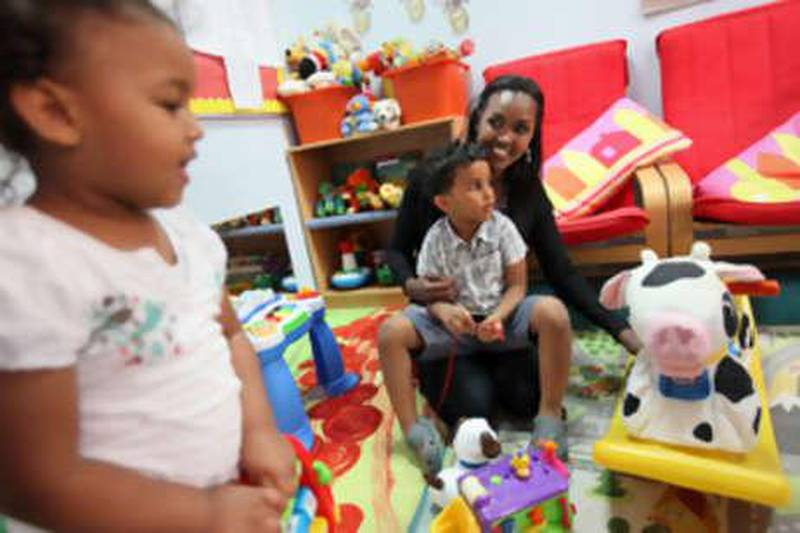 """United Arab Emirates - Abu Dhabi - June 7, 2010.PERSONAL FINANCE: Nimo Abdi (cq-al), 35, plays with her children Zain Harvey (cq-al), 3, center in her lap, and Nawal Harvey (cq-al), 2, left, at the Bright Beginnings Nursery in Abu Dhabi on Monday, June 7, 2010. """"Where we live, we're very lucky. We have the park, the pool and other free facilities,"""" said Abdi, who works at the British Embassy on how she and her family save. """"The beach is a fantastic place to go to for free."""" Amy Leang/The National"""
